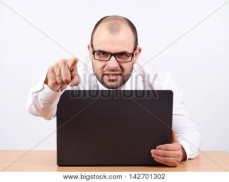 Angry  Businessman Sitting At His Desk And Screaming