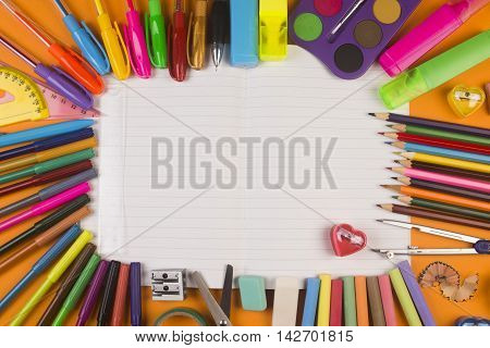 Different school supplies are on white blank notebook.