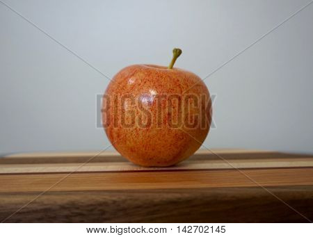 Solitary red apple on patterned cutting board