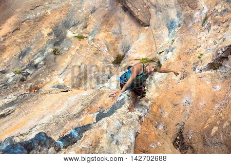 Cute Woman doing Exercise climb natural rock preparing for next Move Top View