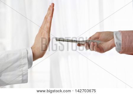 Doctor refusing money offered by woman on light background