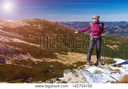 Female Hiker standing on snowy Rocks admiring scenic Winter Mountain View carrying Backpack and walking Pole Sun shining
