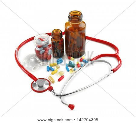 Stethoscope with colourful pills isolated on white