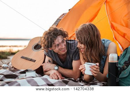 Happy young couple lying and drinking tea in touristic tent on the beach
