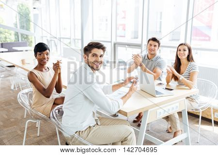 Group of cheerful young business people sitting and clapping hands during presentation in office