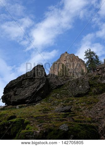 A steep boulder covered hill in Central Oregon leads to d spectacular rock formation on a sunny day.