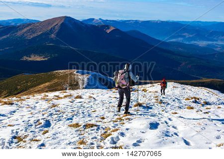 Winter Mountain Range View and Group of Trekkers Walking on Snow Trail Carrying Backpacks and Using Hiking Poles Clear Blue Sky