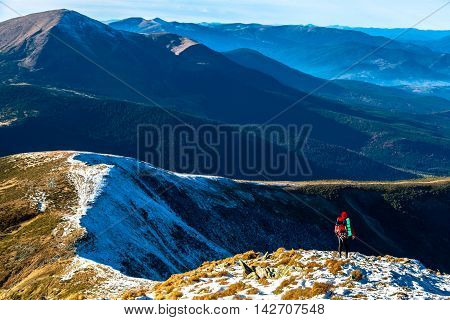 Body of Hiker bright sporty Clothing staying over Mountain Precipice foggy Peaks stacked on distant background covered Snow and Forest