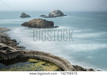 Foggy Ruins of Sutro Baths, San Francisco, California, USA. Dramatic misty fog over Sutro Bath historical landmark in San Francisco.