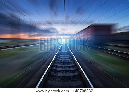 Railway Station With Cargo Wagons In Motion Blur Effect At Sunset