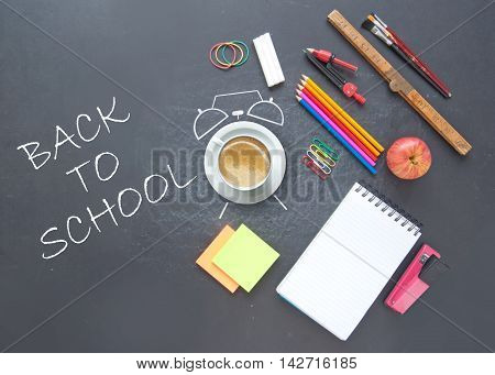 Back to school background with alarm clock drawn around a coffee cup and stationery accessories