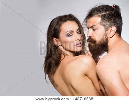 young naked couple of sexy woman with makeup on pretty face and brunette hair with bare shoulders on body back and handsome bearded man with long beard in studio copy space