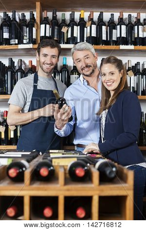 Confident Couple And Salesman With Wine Bottle