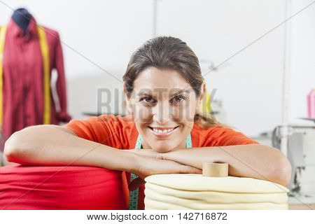 Confident Tailor Leaning On Textile Spools