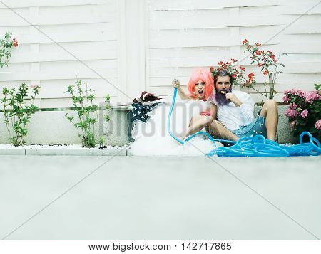 Young girl with pretty smiling face pink hair in beautiful dress holding blue hose sitting on ground with handsome bearded man with lollipop in his hand near flowers on white background copyspace