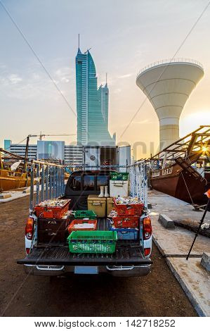 MANAMA, BAHRAIN - MARCH 11, 2016: A pickup vehicle loaded with fresh fish in Manama Fishing Harbour, getting ready to be delivered in the market with Bahrain Financial Harbour in the soft background