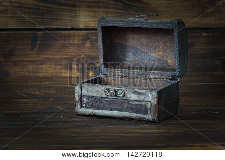 Ancient chest with open lid on dark wooden background
