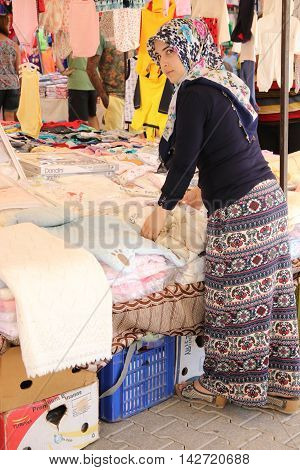 CALIS, TURKEY,17TH JULY 2016:  A female turkish trader selling her fabrics and textiles in a local market in calis, turkey 17th july 2016