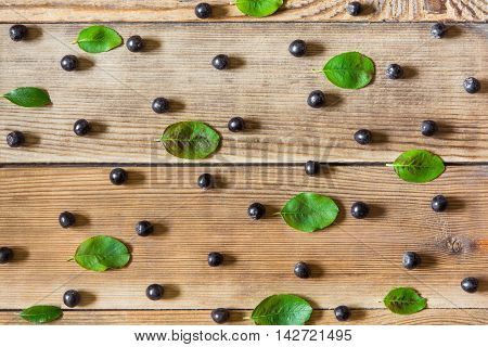 Aronia berries (black chokeberry) and leaves on wooden background in rustic style. Top view.