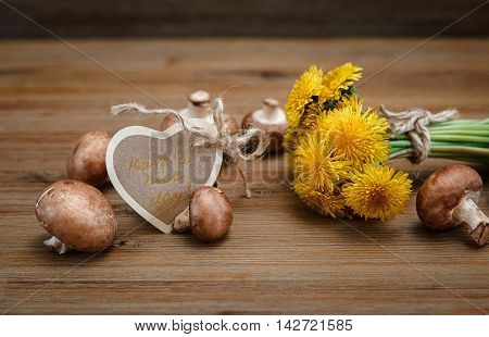Bouquet of Yellow Dandelions,Fresh Mushrooms on the Wooden Table.Wish Card.Garden's Background.Selective Focus