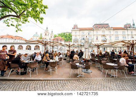 Ljubljana, Slovenia - May 6, 2016: People sitting at the cafe near Ljubljanica river in the old city centre in Ljubljana. Ljubljana is a popular tourist destination in Slovenia.