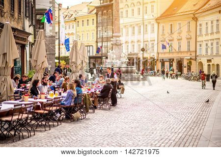 Ljubljana, Slovenia - May 6, 2016: People sitting at the cafe in the old city centre near the city hall in Ljubljana. Ljubljana is the capital of Slovenia and famous european tourist destination.
