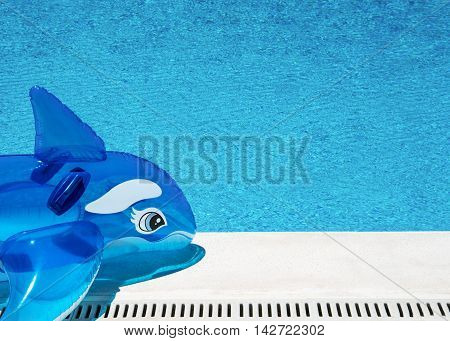 happy summer vacation background selective focus of an inflatable dolphin by a poolside on a bright sunny day with copy space in the swimming pool and on the edge