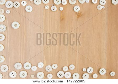 Frame border made of old vintage buttons on wooden table. Copy space for text