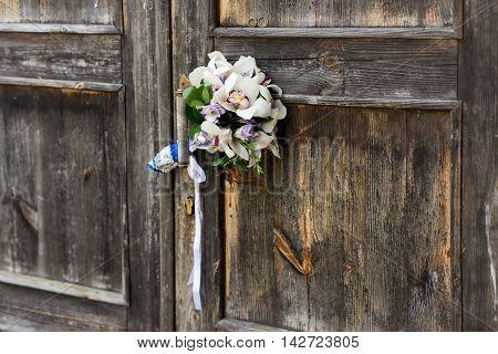 Wedding bouquet on a gray wooden door, tucked behind the handle