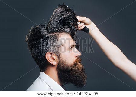 Female Hand Combing Bearded Man