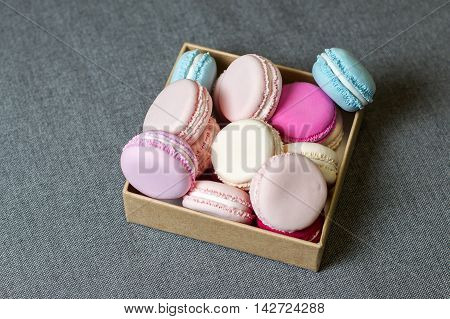 Multi-colored macaron from polymer clay in a box on the background of gray fabric