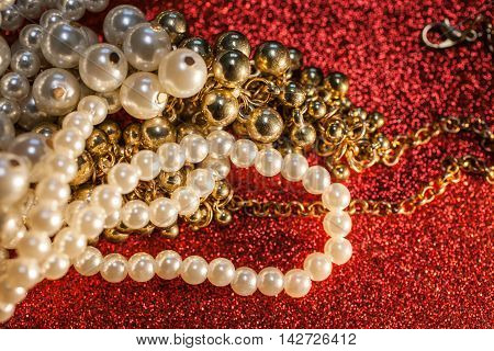 Close up of beautiful pearls necklace against a red glitter. Luxury jewelry background