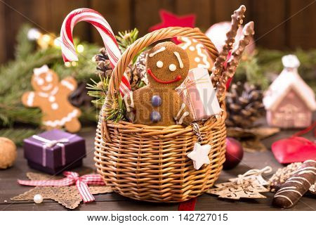 Basket of various Christmas treats gingerbread man gifts and decorations on the table