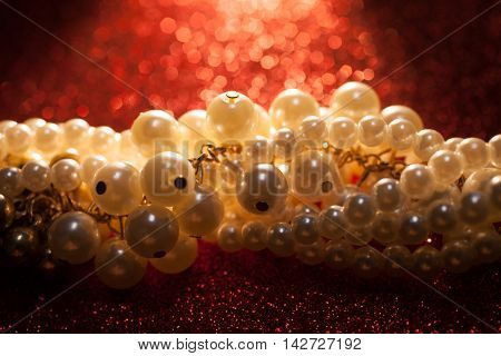 Beautiful creamy pearls on a red sparkling background. Luxury jewelry background