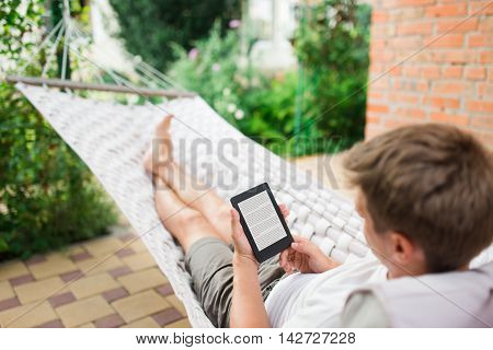 Man using a e-book with lorem ipsum text on screen while relaxing in a hammock