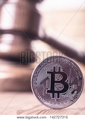 Bitcoin out of law concept. On background of gavel. Toned