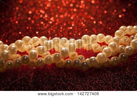 Beautiful creamy pearls on a red glitter background