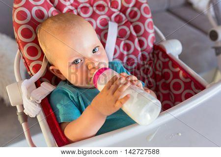 Baby girl drinking milk from the bottle