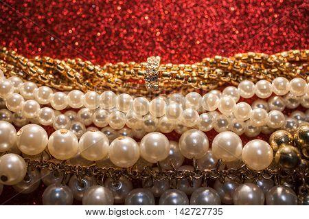 Luxury beautiful jewelry on a red glitter shiny background.