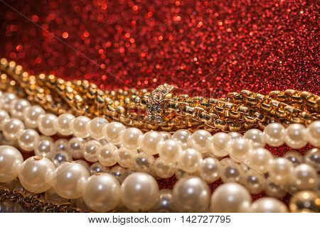 Close up of luxury beautiful jewelry on a red shiny background.