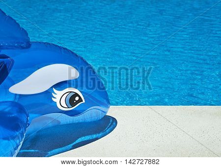 Bright colorful summer vacation background showing an inflatable dolphin at the side of the pool on a sunny warm day ideal for copy space and text made easier from selective focus