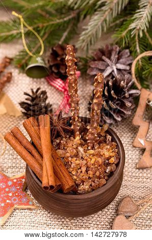 Bowl of caramelized sugar with cinnamon and chocolate sticks on a holiday table
