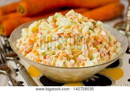 Salad with carrot and crab sticks close up selective focus