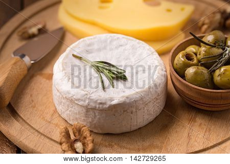 Brie cheese with olives and knife on wooden plate