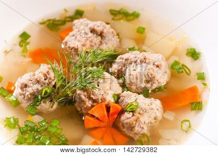 Broth with meatball on the served table