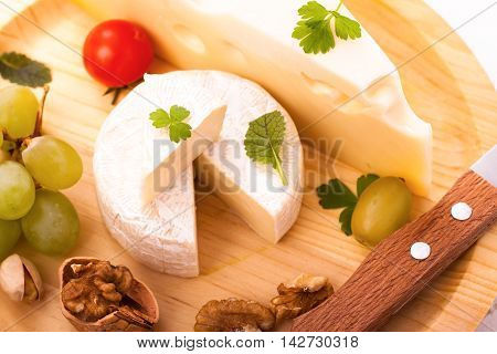 Brie with knife and grapes and walnuts on wooden plate