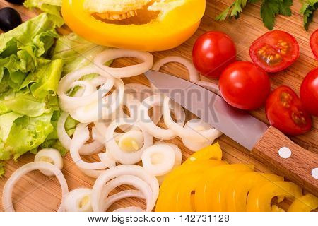 Chopped vegetables with knife on cutting board closeup