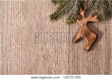 Christmas decoration with fir branch and wooden deer at top right corner of crafts textile background