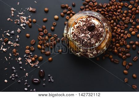 Tiramisu dessert in glass with chocolate and coffee beans on dark background toning selective focus top view with copy space