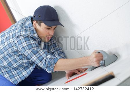 male carpenter sets the baseboard on the floor
